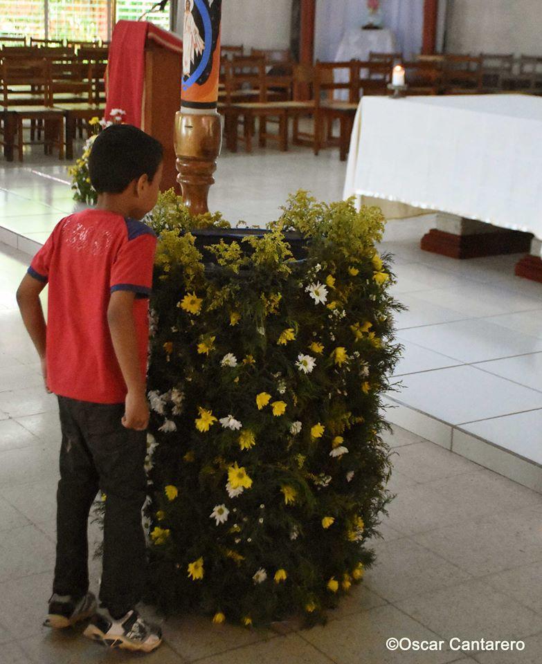 El bautismerio enmascarado con flores... al fondo el vulgar piso y el nuevo altar.